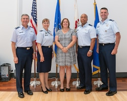 Airmen and state representative posing for photo.