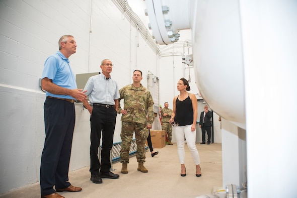 Two men and a woman in civilian attire stand with a man in an Air Force uniform near white industrial tanks in a water treatment facility.