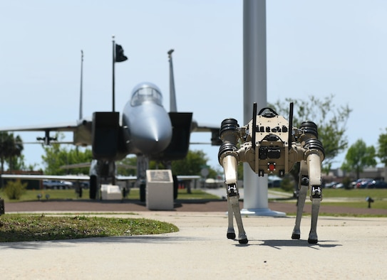 An Unmanned Quad-legged Ground Vehicle stands in front of a jet