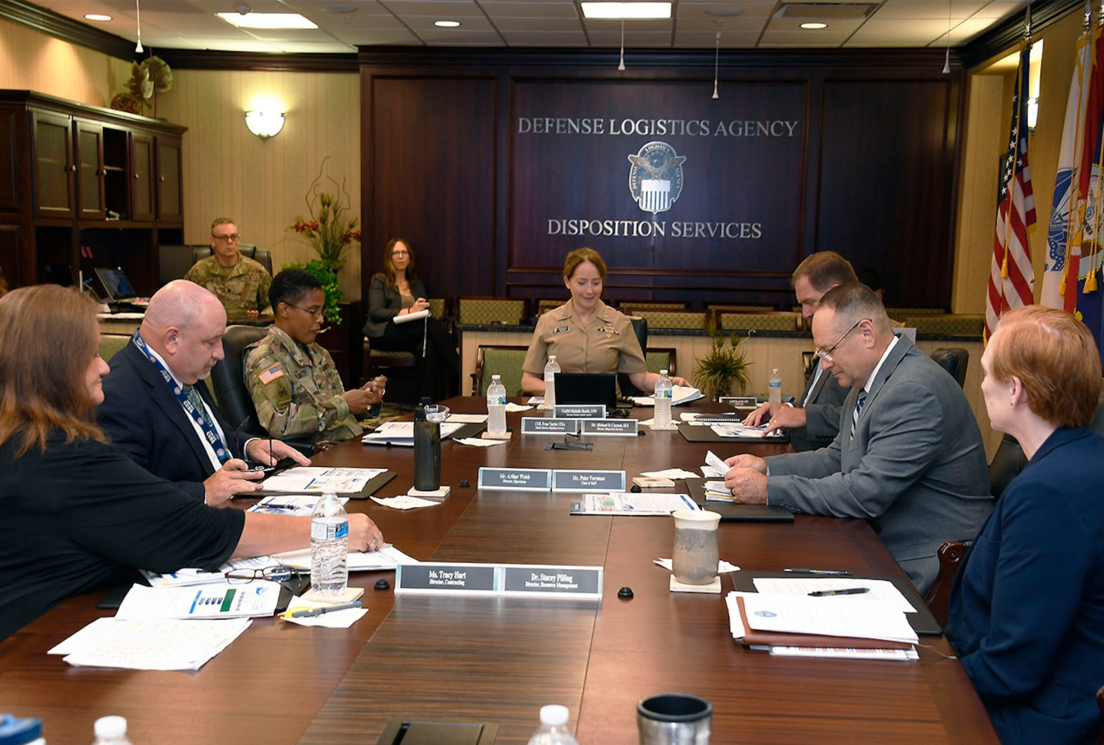 Group of DLA employees sit at conference table.