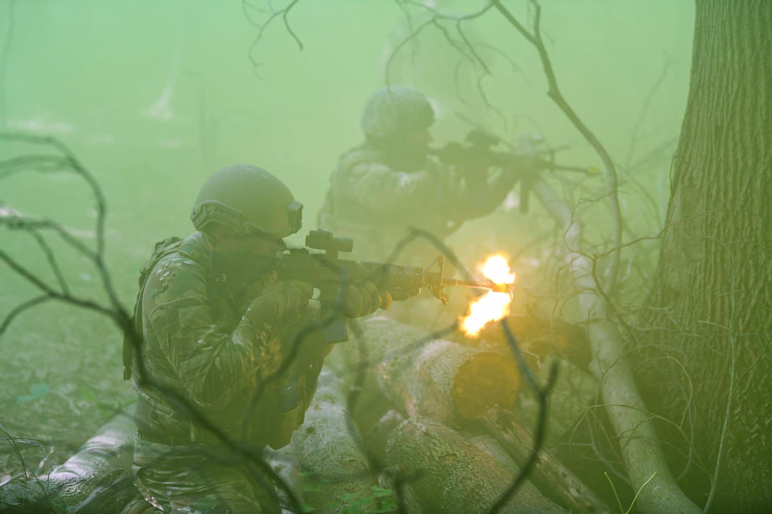 Two airmen fire weapons in a wooded area while surrounded by green smoke.
