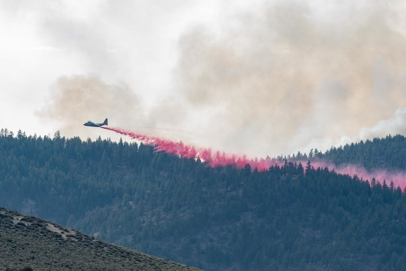 An aircraft moves across a green landscape, leaving behind a trail of red fire retardant.