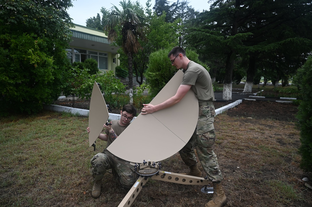 U.S. Air Force Staff Sgt, Brenden Lowe, 1st Combat Communications Squadron radio frequency transmission systems supervisor, left, and Airman First Class Isaac Peebles, 1st CBCS radio frequency transmission systems, build a tactical satellite during exercise Agile Spirit 21