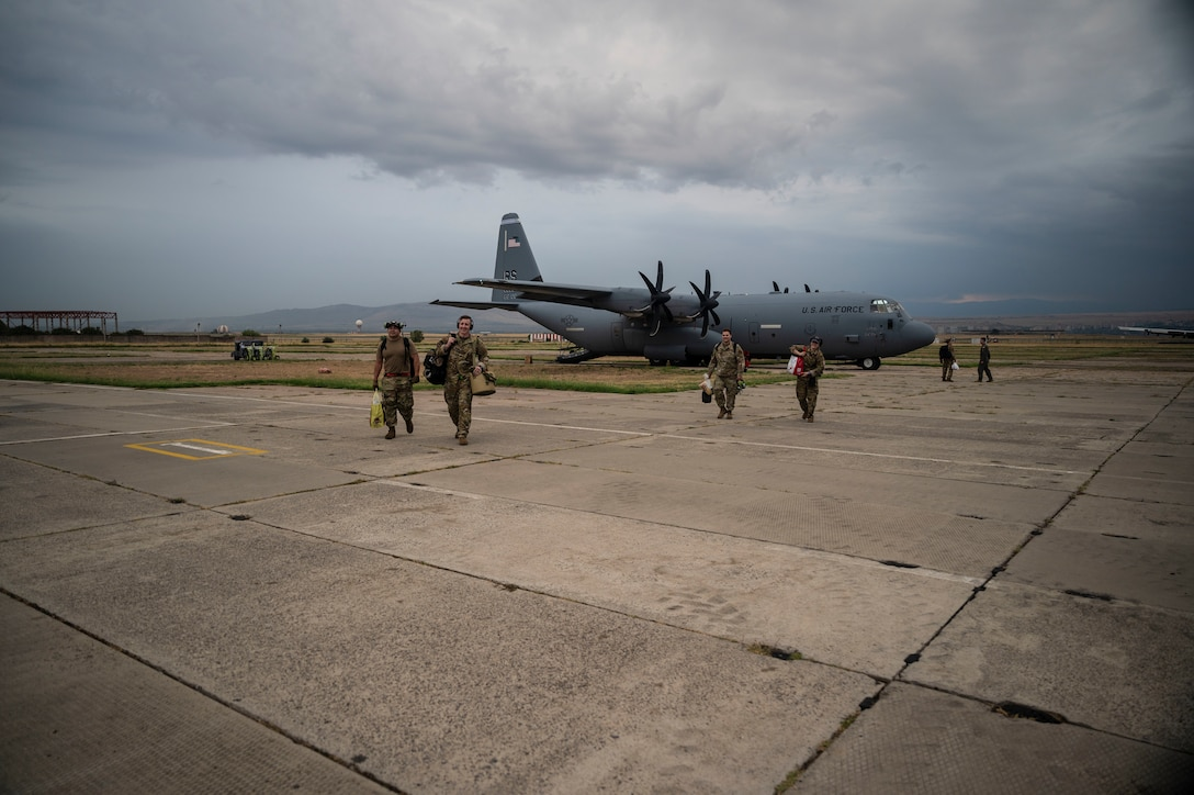 U.S. Air Force Airmen assigned to Ramstein Air Base, Germany, walk across the flight line during exercise Agile Spirit 21