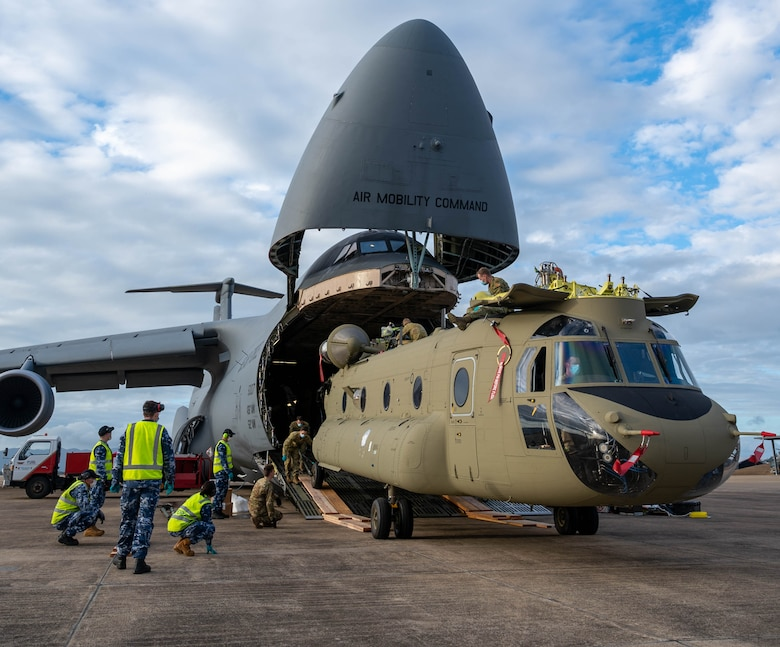 A CH-47F Chinook helicopter is unloaded from a Dover Air Force Base C-5M Super Galaxy at Royal Australian Air Force Base Townsville, Australia, July 7, 2021. The C-5 transported two CH-47F Chinook helicopters to RAAF Base Townsville as a part of the Department of Defense's Foreign Military Sales program.