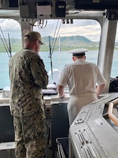CNO Gilday and the Commanding Officer of USS Charleston look out the windows of the bridge of the ship.