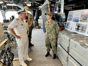 CNO Gilday speaks to a Sailor in front of a display.