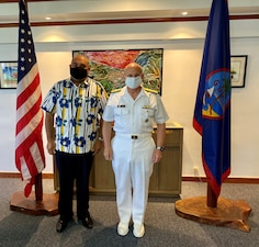 CNO Gilday and Acting Guam Governor pose for a photo in front of Guam and US flags.