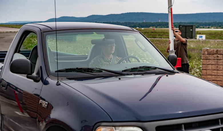 U.S. Air Force Senior Airman James Jones, a controlled movement area escort and project manager assigned to the 86th Civil Engineering Squadron,  drives past a barrier arm at Ramstein Air Base, Germany, July 27, 2021. Jones coordinated with multiple squadrons to upgrade the security of the airfield by replacing old security barriers with new barrier arms, increasing airfield security. (U.S. Air Force photo by Airman Jared Lovett)