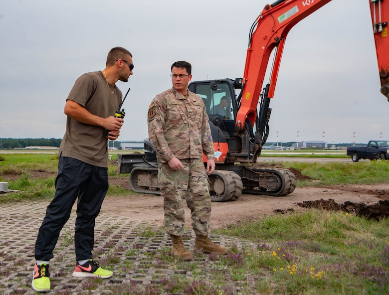 U.S. Air Force Senior Airman James Jones, a controlled movement area escort and project manager assigned to the 86th Civil Engineering Squadron,  talks to an escort augmentee at a construction site at Ramstein Air Base, Germany, July 27, 2021. Escort workers make sure that the contractors do not cross over restricted area lines and stay away from certain areas when planes are landing for security and safety of everyone on the airfield.  (U.S. Air Force photo by Airman Jared Lovett)