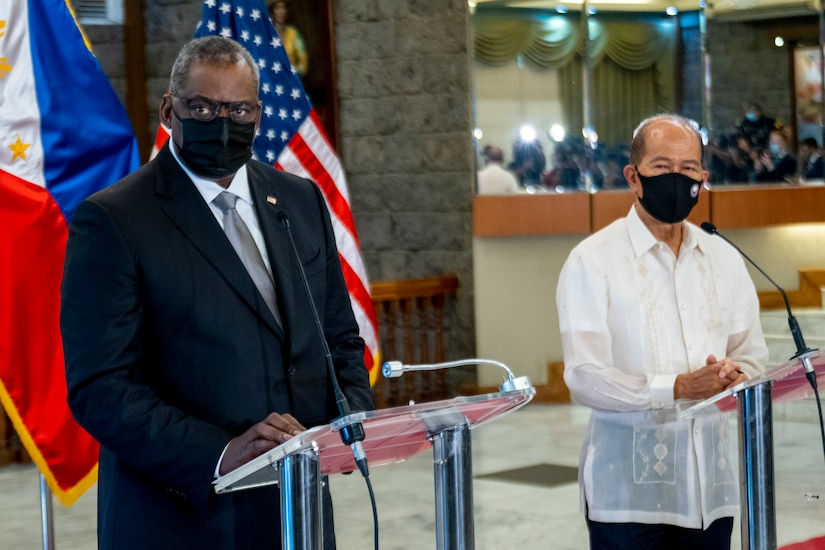 Two men stand next to each wearing masks.