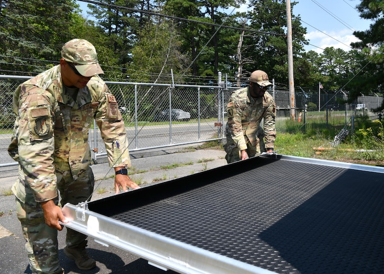 Master Sgt. Wayne Wilson and Master Sgt. Sandy Singleton, 104th Security Forces Squadron members close the back of a domestic operations trailer on July 27, 2021 at Barnes Air National Guard Base. The trailers are compact enough to fit inside C-130, C-17 and C-5 aircraft and quickly deployable to all locations worldwide via air or land. (U.S. Air National Guard Photo by Senior Airman Camille Lienau)
