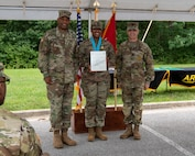 three soldiers posing for a photo in front of flags.