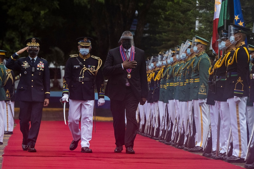 Several men walk along a red carpet in front of a row of service members.