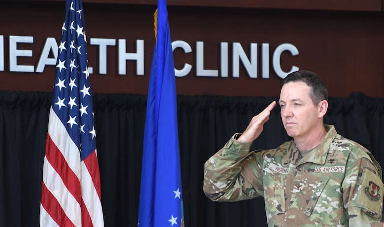 Man saluting with American and Air Force flags in the background