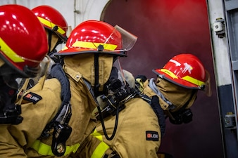 Sailors participate in a firefighting evolution during a general quarters drill aboard the Nimitz-class aircraft carrier USS Carl Vinson (CVN 70).