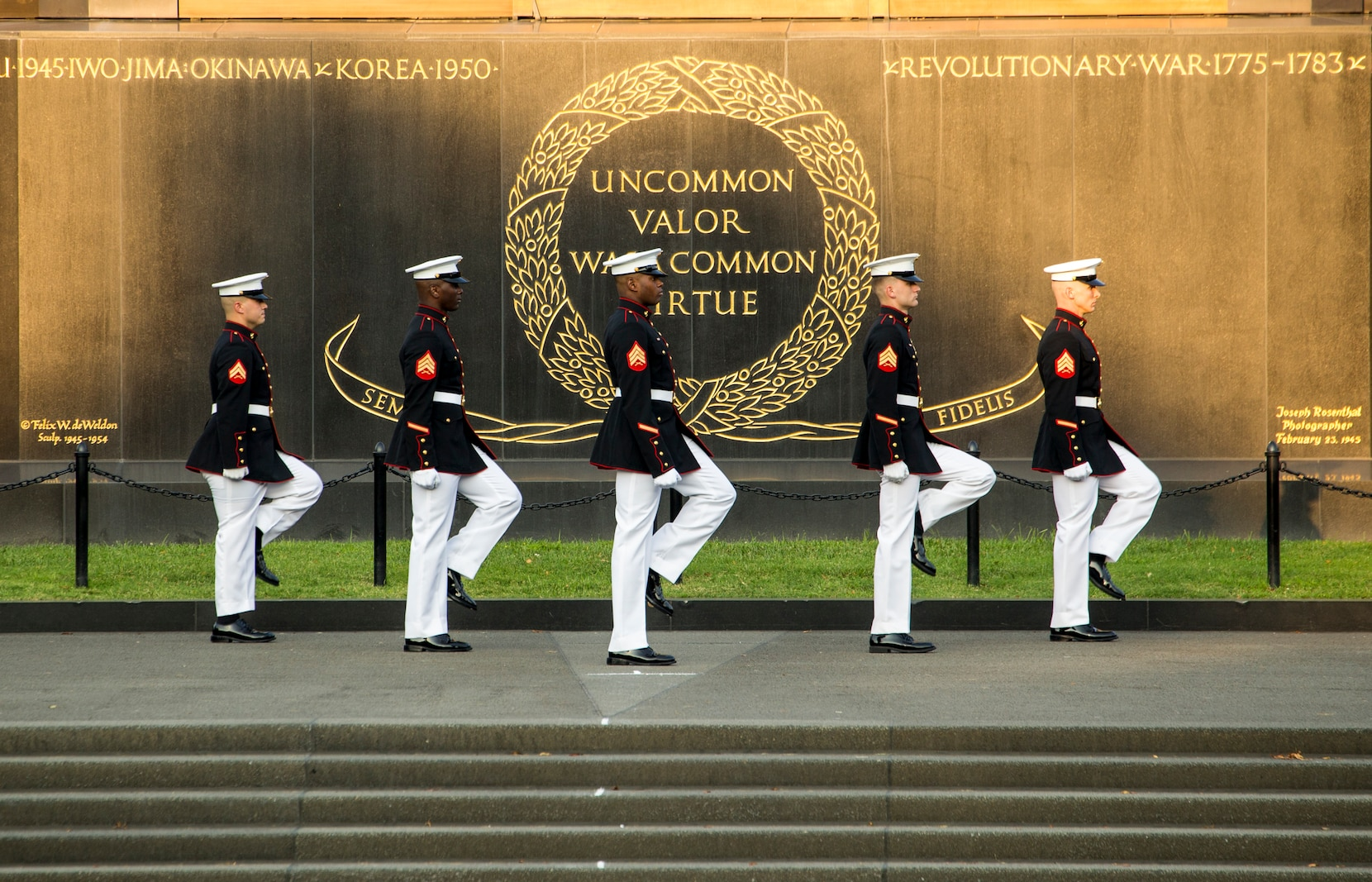 Marines with the parade staff march into position during the Non-Commissioned Officer Tuesday Sunset Parade at the Marine Corps War Memorial, Arlington, Va., July 27, 2021.