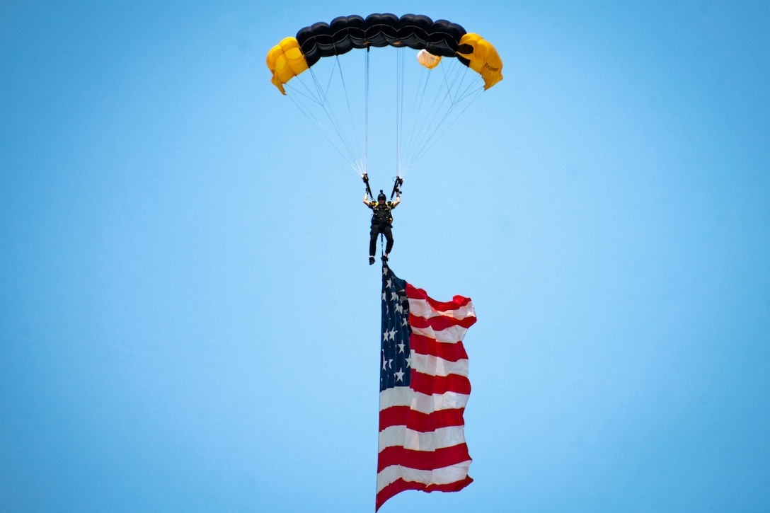 An American flag dangles below a man parachuting to the ground.