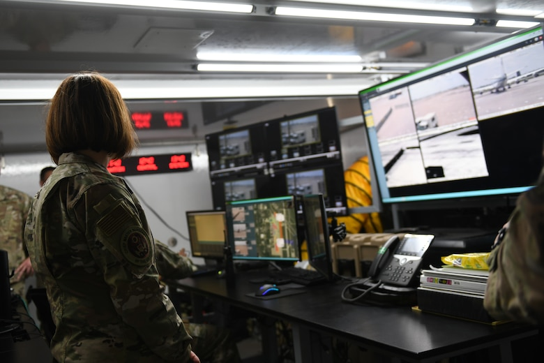 Chief Master Sergeant of the Air Force JoAnne S. Bass looks at television monitors in the mobile base defense operations center.