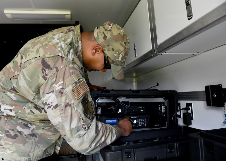 Master Sgt. Wayne Wilson, 104th Security Forces Squadron member adjusts the radio inside of a domestic operations trailer on July 27, 2021 at Barnes Air National Guard Base. The built-in radio system allows for communication between SFS members and civilian law enforcement agencies. (U.S. Air National Guard Photo by Senior Airman Camille Lienau)