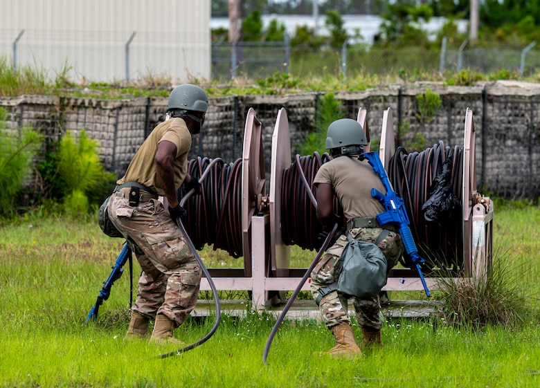 Photo of two Airmen pulling a cable