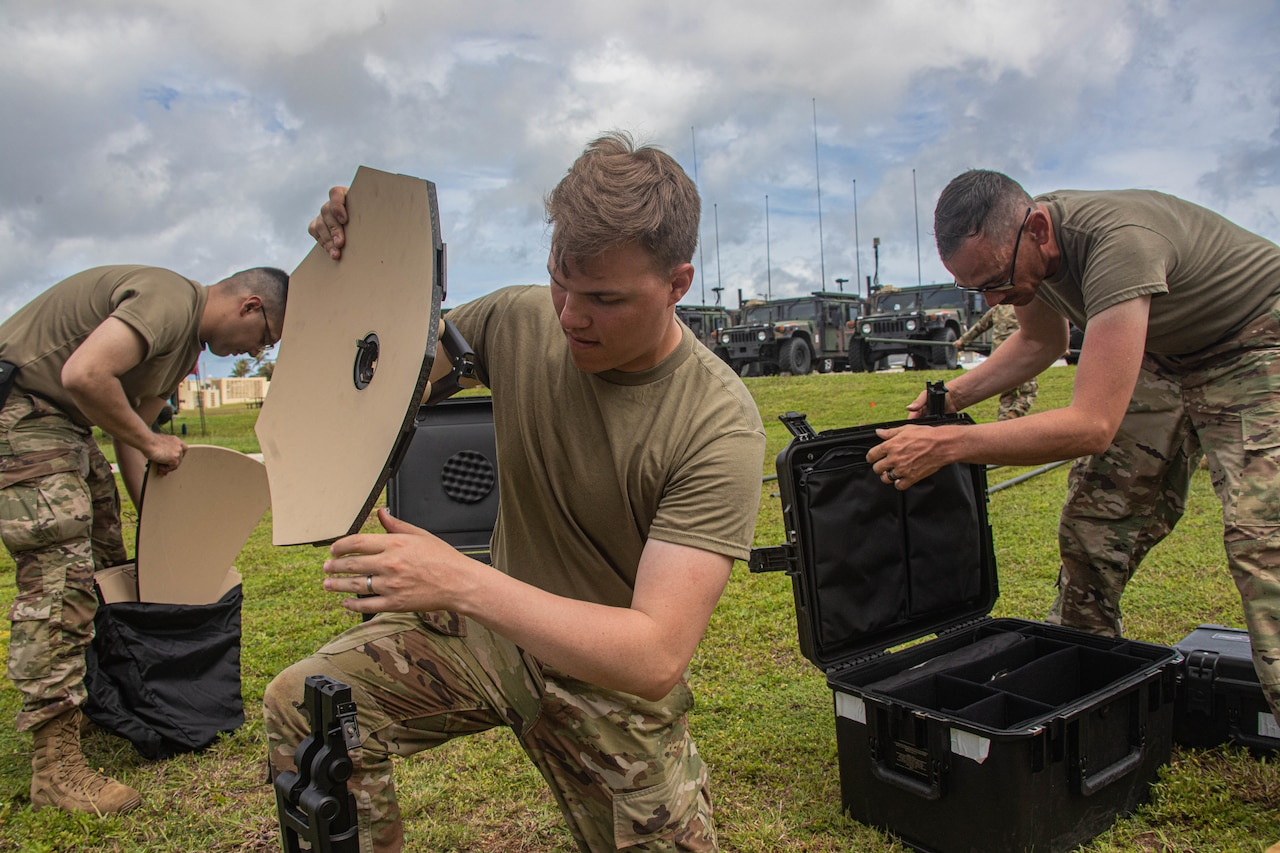 Three young soldiers set up equipment.