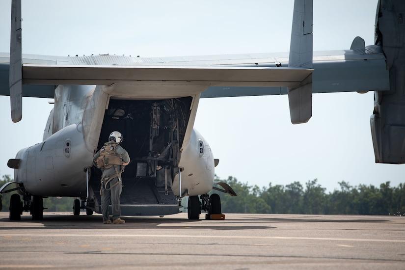 A person stands beside an aircraft.