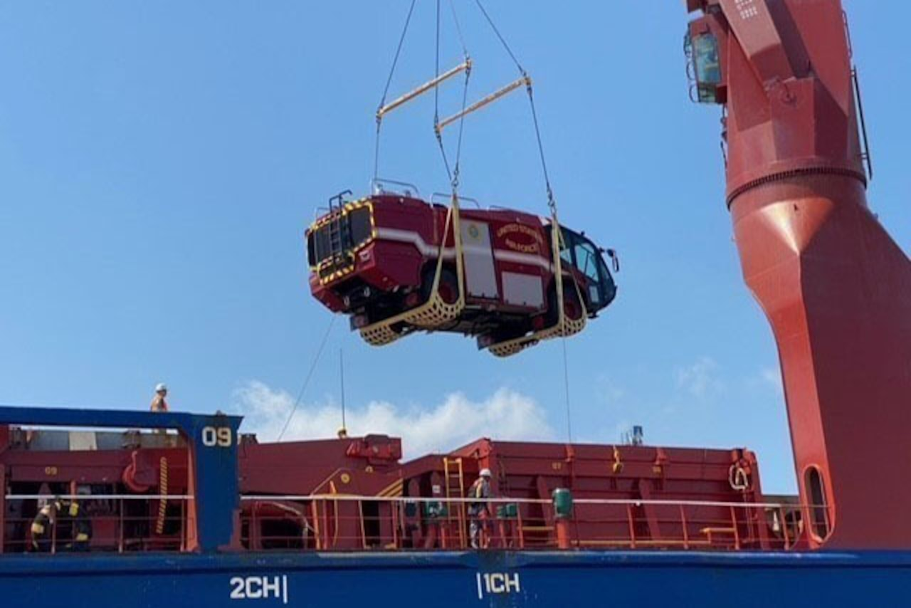 A large item is hoisted onto a ship.