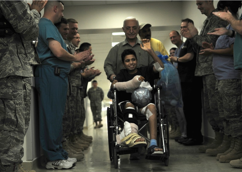 Medical personnel applaud as victim of a mortar explosion leaves the Air Force Theater Hospital