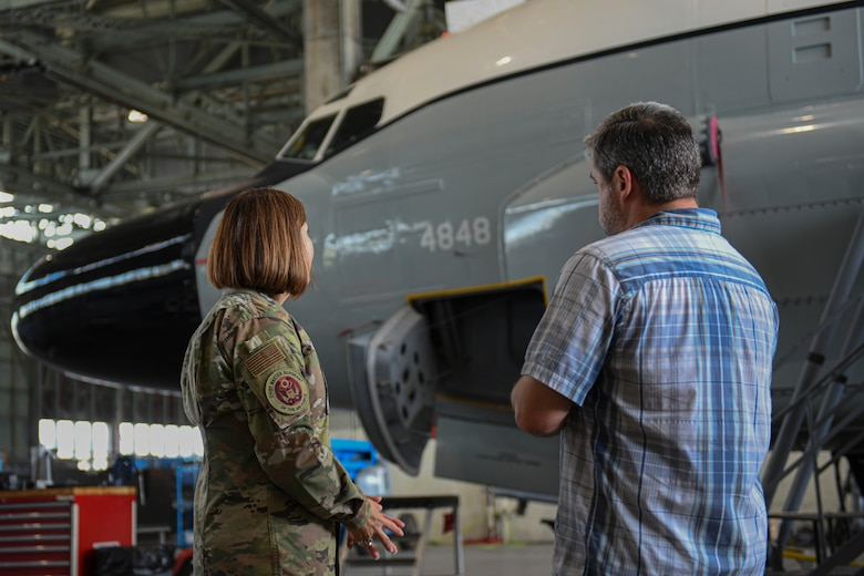 Chief Master Sergeant of the Air Force JoAnne S. Bass looks at a rc-135V/W Rivet Joint aircraft as a man talks to her.