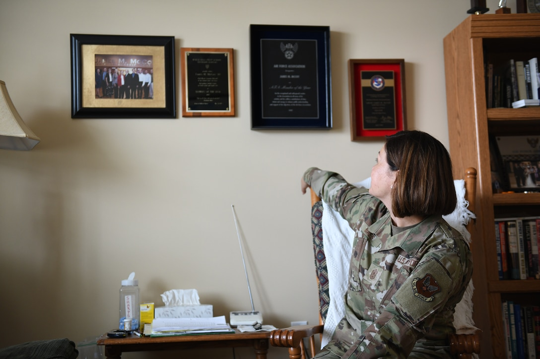 Chief Master Sergeant of the Air Force JoAnne S. Bass sits in a chair with her arm on the back rest turned over her right shoulder looking at the wall behind her. The wall behind her has four frames, one photo and three awards.