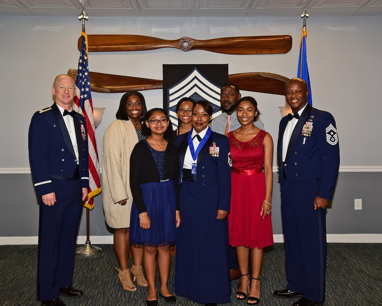 U.S. Air Force Senior Master Sgt. Joi T. Washington, 14th Force Support Squadron superintendent (center) and family, pose for a photo with Col. Seth W. Graham, 14th Flying Training Wing commander (left) and Chief Master Sgt. Antonio Cooper, 14th Flying Training Wing command chief, at the Chief Induction ceremony, July 22, 2021 on Columbus Air Force Base, Miss. Washington provided administrative oversight to multiple personnel and family support offices within the 14th Force Support Squadron during her assignment to CAFB. Washington departed CAFB in July 21 during a Permanent Change of Station. (Multimedia Services photo by Melissa A. Duncan-Doublin)