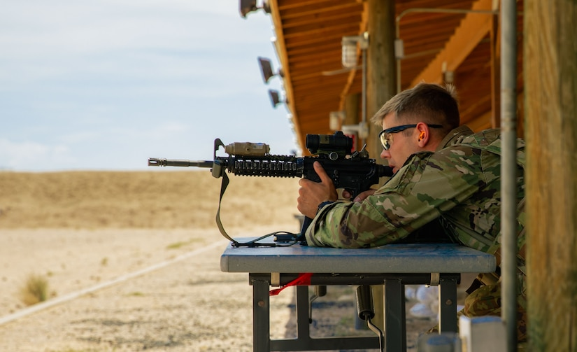 A soldier aims his weapon at a target.