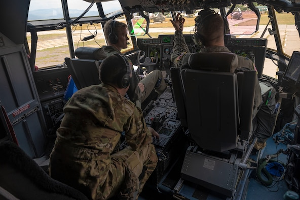 Three U.S. Air Force pilots assigned to the 37th Airlift Squadron conduct pre-flight checks in a C-130J Super Hercules aircraft during exercise Agile Spirit 21