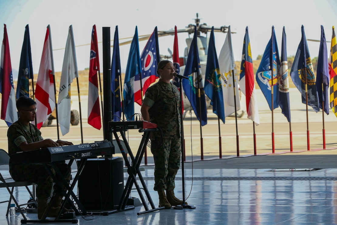 U.S. Marine Corps Cpl. Megan Browning, a musician with Marine Wing Headquarters Squadron 3, 3d Marine Aircraft Wing sings during a change of command ceremony on Marine Corps Air Station Yuma, Ariz., June 15, 2021. Sgt. Maj. Larry Buenafe was relieved of his duty as Marine Operational Test and Evaluation Squadron 1 sergeant major by Sgt. Maj. Frank Gratacos. (U.S. Marine Corps photo by Lance Cpl. Gabrielle Sanders)