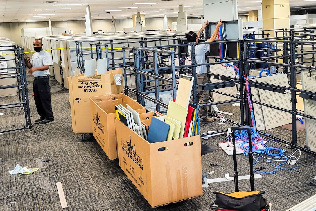 Contractors take apart and remove cubicles in the Air Force Installation and Mission Support Center headquarters building July 29 in San Antonio.