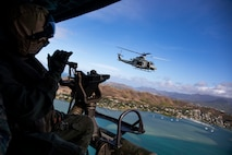 A U.S. Marine Corps crew chief with Marine Light Attack Helicopter Squadron 367 waves at a fellow UH-1Y Venom utility helicopter during an Intrepid Tiger II exercise, Marine Corps Training Area Bellows, Oahu, July 22, 2021. The Intrepid Tiger II Electronic Warfare capability embodies Marine Corps Base Hawaii's goal to modernize resources to provide the tools required to ensure the readiness of the individual warfighter. (U.S. Marine Corps photo by Lance Cpl. Samantha Sanchez)