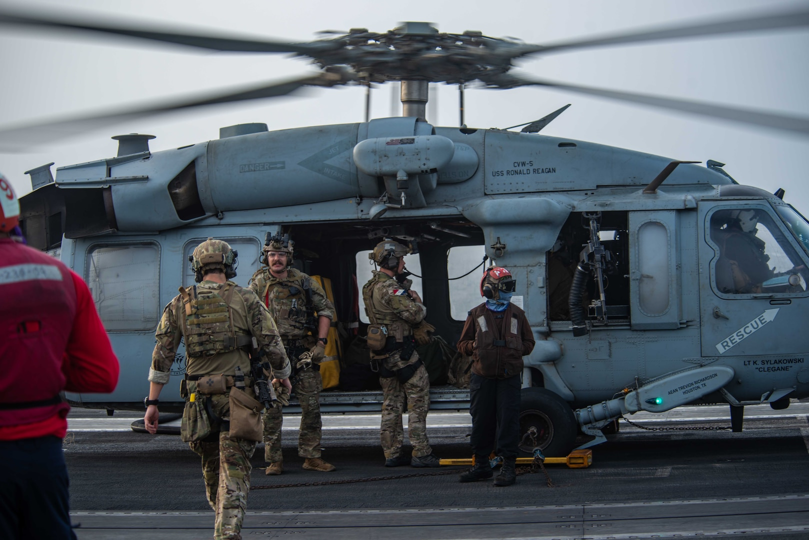 """210730-N-WS494-1238 ARABIAN SEA (July 30, 2021) – Sailors assigned to Explosive Ordnance Disposal Mobile Unit (EODMU) 5 board an MH-60S Sea Hawk helicopter, attached to the """"Golden Falcons"""" of Helicopter Sea Combat Squadron (HSC) 12, on the flight deck of aircraft carrier USS Ronald Reagan (CVN 76) in response to a call for assistance from a vessel in distress in the Arabian Sea, July 30. Ronald Reagan is deployed to the U.S. 5th Fleet area of operations in support of naval operations to ensure maritime stability and security in the Central Region, connecting the Mediterranean and Pacific through the western Indian Ocean and three strategic choke points. (U.S. Navy photo by Mass Communication Specialist 2nd Class Quinton A. Lee)"""