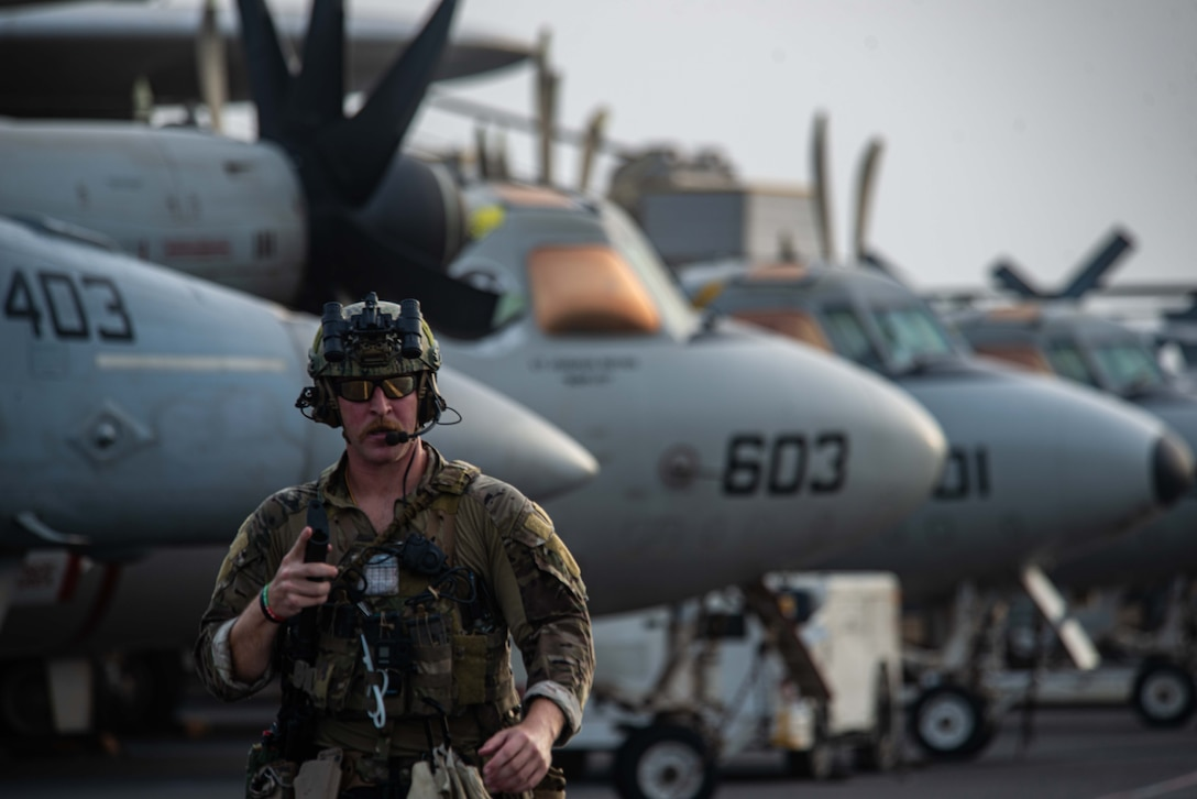 210730-N-WS494-1258 ARABIAN SEA (July 30, 2021) –Explosive Ordnance Disposal Technician 3rd Class Ethan Tews, assigned to Explosive Ordnance Disposal Mobile Unit (EODMU) 5, walks across the flight deck of aircraft carrier USS Ronald Reagan (CVN 76) in response to a call for assistance from a vessel in distress in the Arabian Sea, July 30. Ronald Reagan is deployed to the U.S. 5th Fleet area of operations in support of naval operations to ensure maritime stability and security in the Central Region, connecting the Mediterranean and Pacific through the western Indian Ocean and three strategic choke points. (U.S. Navy photo by Mass Communication Specialist 2nd Class Quinton A. Lee)