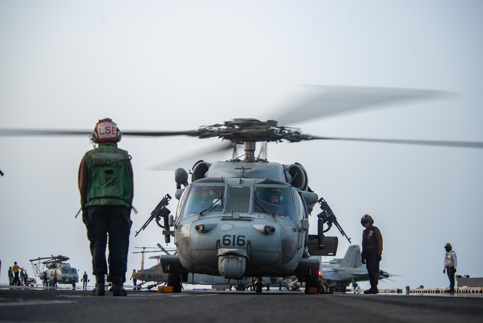 """210730-N-WS494-1288 ARABIAN SEA (July 30, 2021) – Sailors prepare an MH-60S Sea Hawk helicopter, attached to the """"Golden Falcons"""" of Helicopter Sea Combat Squadron (HSC) 12, to launch on the flight deck of aircraft carrier USS Ronald Reagan (CVN 76) in response to a call for assistance from a vessel in distress in the Arabian Sea, July 30. Ronald Reagan is deployed to the U.S. 5th Fleet area of operations in support of naval operations to ensure maritime stability and security in the Central Region, connecting the Mediterranean and Pacific through the western Indian Ocean and three strategic choke points. (U.S. Navy photo by Mass Communication Specialist 2nd Class Quinton A. Lee)"""