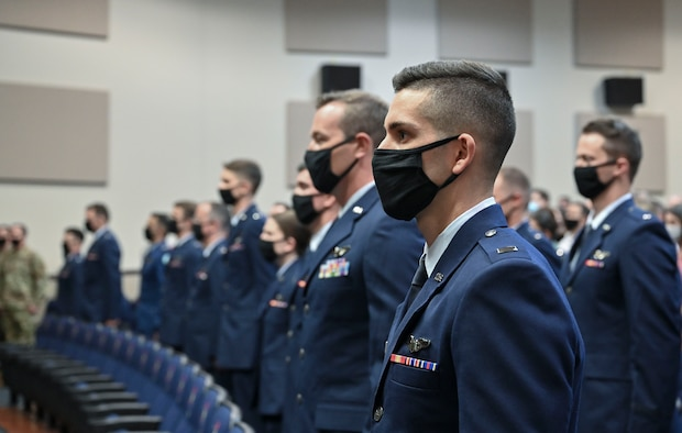 Graduates from the Specialized Undergraduate Pilot Training class 21-13, stand at attention during the National Anthem, July 30, 2021, on Columbus Air Force Base, Miss. A total of 30 aviators earned the title of U.S. Air Force Pilot, after completing a 52-week SUPT course. (U.S. Air Force photo by Airman 1st Class Jessica Haynie)