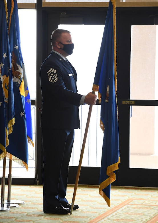 U.S. Air Force Chief Master Sgt. Adam Vizi, Second Air Force command chief holds the guidon during the Second Air Force change of command ceremony inside the Bay Breeze Event Center at Keesler Air Force Base, Mississippi, July 30, 2021. The ceremony is a symbol of command being exchanged from one commander to the next. Maj. Gen. Andrea Tullos relinquished command of the Second Air Force to Maj. Gen. Michele Edmondson. (U.S. Air Force photo by Kemberly Groue)