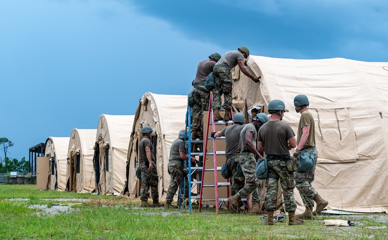Photo of Airmen pinning a cover on a temporary shelter