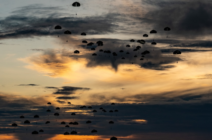 Parachutes descend in a pink- and blue-streaked sky.