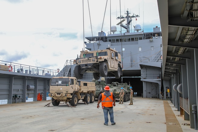 Soldiers load supplies onto a ship.
