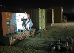 """Chief Warrant Officer 2 Paul Viall, information systems technician, assigned to the 310th Sustainment Command (Expeditionary), works at night with the aid of a projector to trace out the design of the unit mural or unit T-wall, Camp Arifjan, Kuwait.  Viall worked countless hours to paint a mural that will represent the hard work and dedication of the Army Reserve's Indianapolis-based """"Brickyard"""" Soldiers and their time serving within the U.S. Central Command's area of responsibility."""
