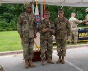 three soldiers in army uniforms standing in front of flags.
