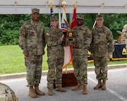 four men and women in army uniforms standing in front of flags.
