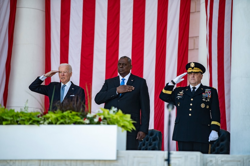 Three men stand at attention in front of large U.S. flags.