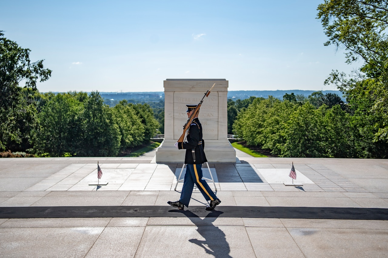 A soldier walks in front of the Tomb of the Unknown Soldier.